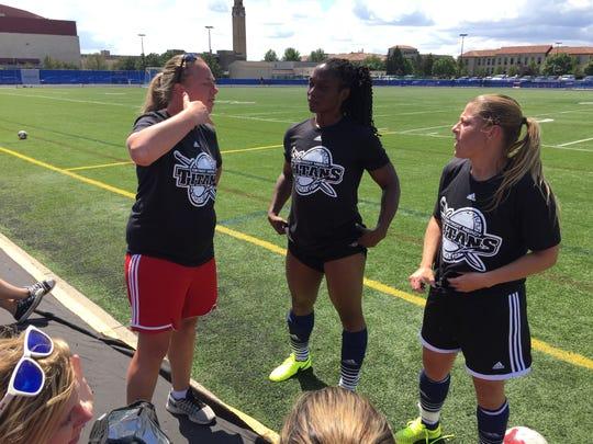 Nathalee Thompson, center, jokes with Detroit Mercy alumni Erika Rust, left, and Anita Novjanovski at Saturday's annual women's soccer alumni game at Titan Field in Detroit.