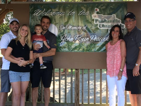 The Peacock family poses in front of a banner that