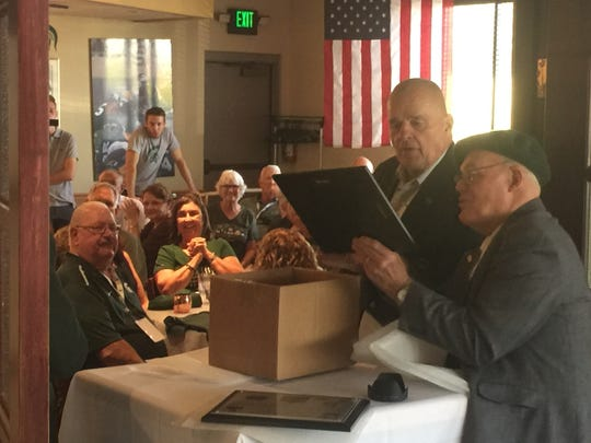 Former Michigan State defensive lineman Pat Gallinagh, right, and Notre Dame offensive lineman George Goeddeke give out plaques to players from the 1966 teams from both schools on Saturday, Sept. 23, 2017 in East Lansing.