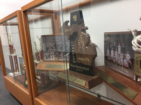 Marshall Academy's 2017 boys basketball Class D district championship trophy sits in a case outside the gymnasium.