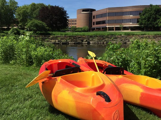 Kayaks sit ready to launch on the Battle Creek River, with the Kellogg Community Foundation in the background.