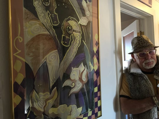 """""""Jungle"""" Jim Gibson stands beside one of the artist renditions of a swan print that will be up for auction Saturday at the Morris Burner Hotel. Proceeds will go toward creating an art program at the Reno/Sparks Gospel Mission."""