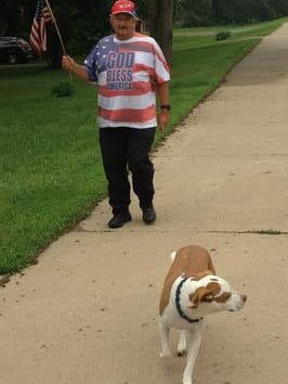 """Colin Campbell, the """"Flag Man of Haslett,"""" walks along Marsh Road with Jayda in 2013"""