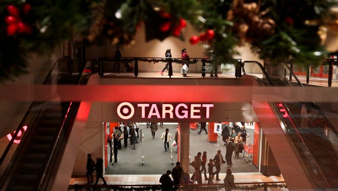 Holiday trimmings greet shoppers around the main entry of a Target on Saturday, Nov. 23, 2013, in New York. Despite signs that the economy is improving, big store chains like Wal-Mart and Kohlís donít expect Americans to have much holiday shopping cheer unless they see bold, red signs that offer huge discounts.
