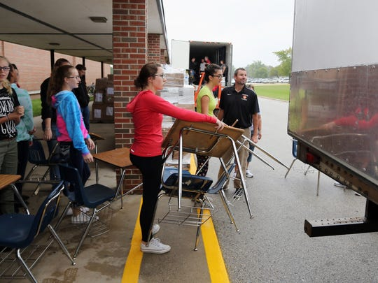 Students wait in line with desks to be packed into