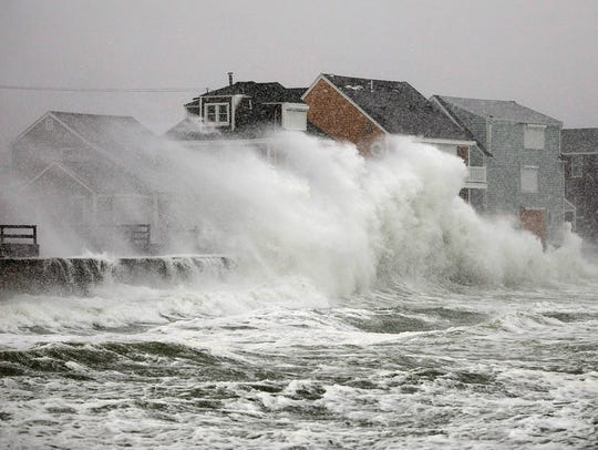 Waves crash over homes along the seawall in Scituate,