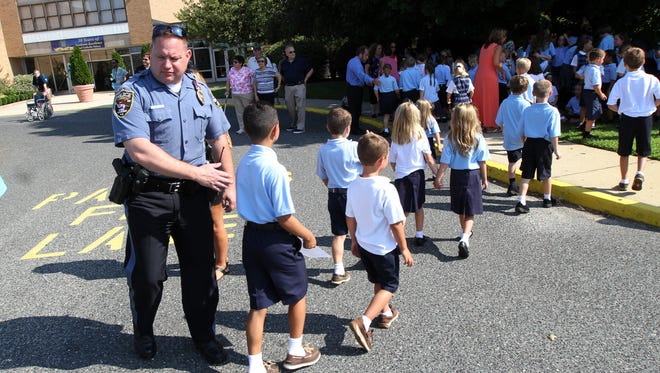 A Brick Township police officer directs St. Dominic school students to the shade outside the school Tuesday, after some were overcome by the heat during a ceremony marking the 50th anniversary of the school opening.