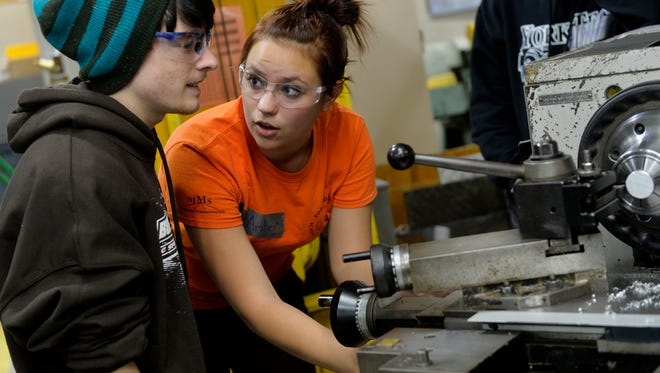 In this 2014 file photo, York Tech senior Amber Billet demonstrates a machine for Ken Porst, 17 of West Manchester Township, in the school's precision metal machining shop during an open house.