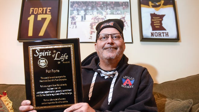 Former Apollo High School head hockey coach Pat Forte holds his Spirit of Life award Tuesday, Dec. 6, in his home in Sartell.