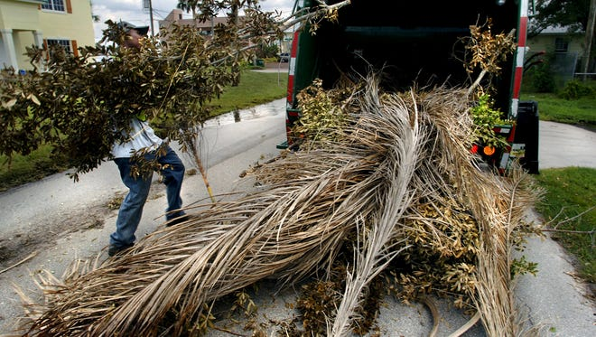 Martin County residents might pay 1.6 percent more for trash collection next fiscal year than this year. In this photo, worker Willgued Mildort picks up tree limbs and other yard debris in Palm City on May 27, 2005.