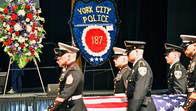 Members of the U.S. Marine Corps and York City Police bear Officer Alex Sable's coffin to the front of his memorial service Friday.