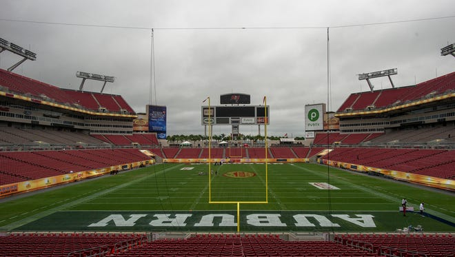 Field crews paint the field at Raymond James Stadium in Tampa Bay, Fla., on Wednesday, Dec. 31, 2014, for the Outback Bowl.