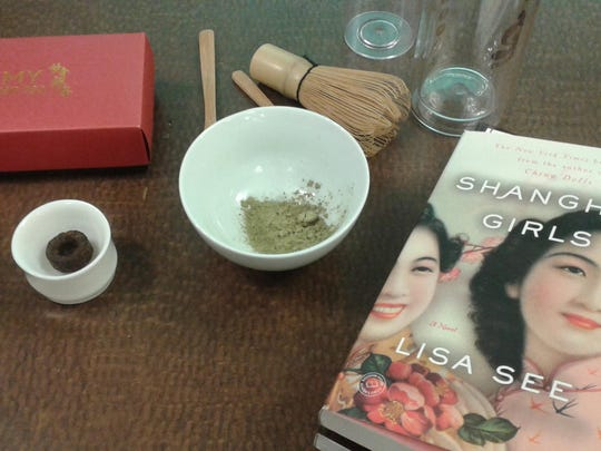 """Pu-erh tea cake (left) with powdered tea and the Everybody's Reading selection for 2016, """"Shanghai Girls,"""" by Lisa See."""
