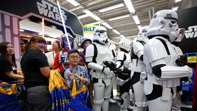 Star Wars fans shop at a toy store at midnight in Hong Kong, on Friday, Sept. 4, 2015.