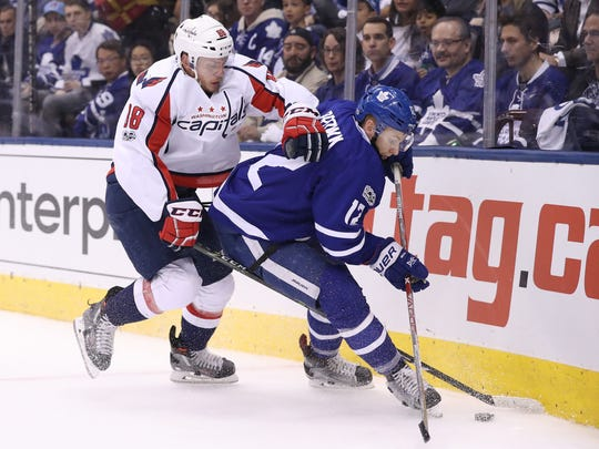 Toronto Maple Leafs right wing Connor Brown, right, tries to gain control of the puck as Washington Capitals defenseman Nate Schmidt defends in game six of the first round of the 2017 Stanley Cup Playoffs at Air Canada Centre in Toronto.