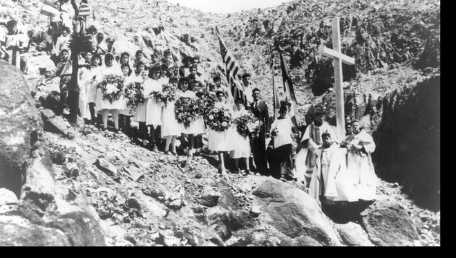 High above the floor of Red Rock Canyon are some of the people who made the pilgrimage to Marcus Uribe's monument to the deceased flyers at its dedication April 30, 1944.