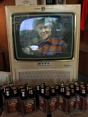 A commercial from the 1980s featuring Curt Gowdy plays on a vintage television.