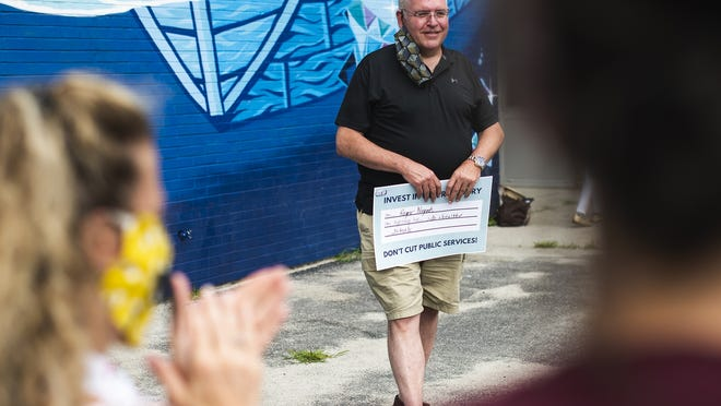 Roger Nugent, president of the Educational Association of Worcester, attends a rally of the Raise Up Massachusetts coalition at Elm Park Community School on July 22.