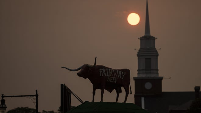 WORCESTER - The sun sets over Fairway Beef and St. John's Church on Temple Street on Wednesday. Smoke from the West Coast wildfires has reached the East Coast, covering the skies in a smoky haze.