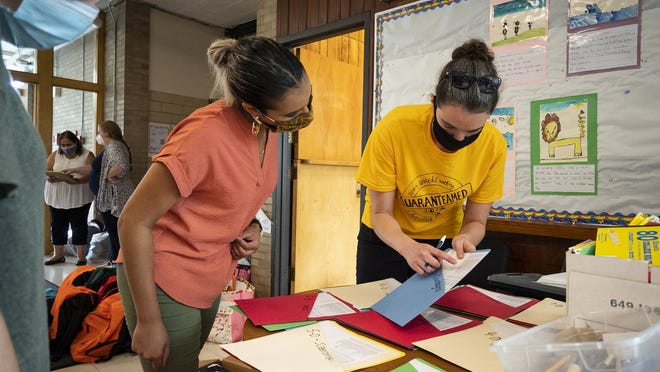 Second-grade teacher Ashley Veras and fifth- and sixth-grade dual language teacher Rachel Gatley try to stay organized while handing out school supplies for students at Chandler Magnet Elementary School in Worcester last week.