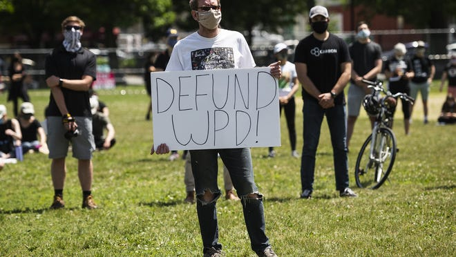 A protester holds a sign that reads 'DEFUND WPD' during the Say Her Name Solidarity March at Cristoforo Colombo Park in Worcester on Saturday.