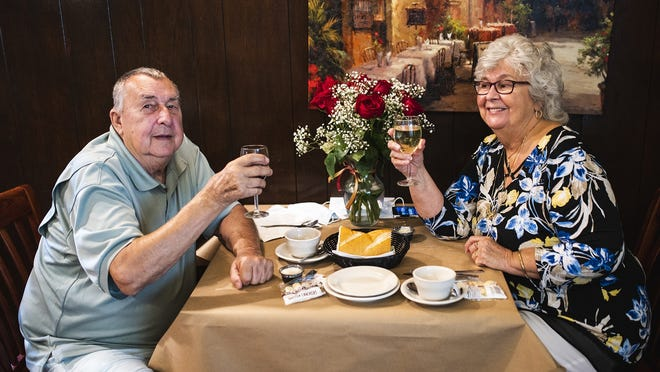 Ronald and Suzanne Yeskevicz raise a glass as they celebrate their 50th wedding anniversary Friday at Il Camino in Leominster. Their children and grandchildren sent the vase of roses to the restaurant for their table.