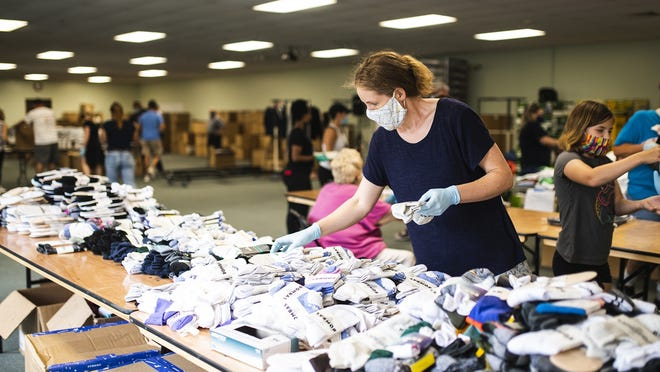 WORCESTER - Michelle Tranes of Hope for Worcester organizes socks as volunteers assemble everyday essential items into Bags of Hope for those battling addiction at the Living Word Church on Saturday.