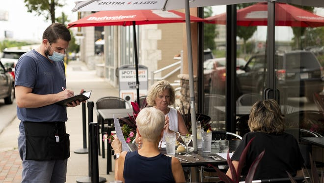 Bartender Tildi Frroku takes an order at one of the outdoor dining tables at Nuovo on Shrewsbury Street in July. The city Wednesday extended the outdoor dining program instituted during the pandemic to help keep restaurants afloat.