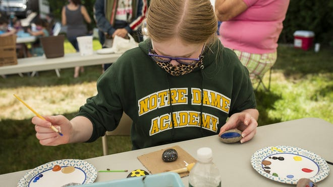 Addison Daly, 12, paints rock during an outdoor art class at the Burncoat Center for Arts and Wellness.
