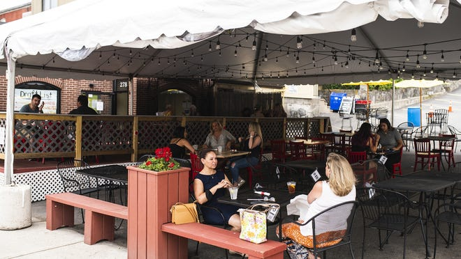 People dine outdoors at the Flying Rhino on Shrewsbury Street in Worcester in July.
