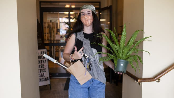 Arms full of plants purchased at Seed to Stem, Brianna Morin exits Crompton Collective with goodies during the state's 14th sales tax holiday on Saturday.