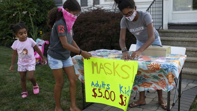 WORCESTER - Rebecca Mariano, 4, looks on while older sisters Lauren, 10, and Julie, 14, adjust the sign on their mask stand outside their home Friday.