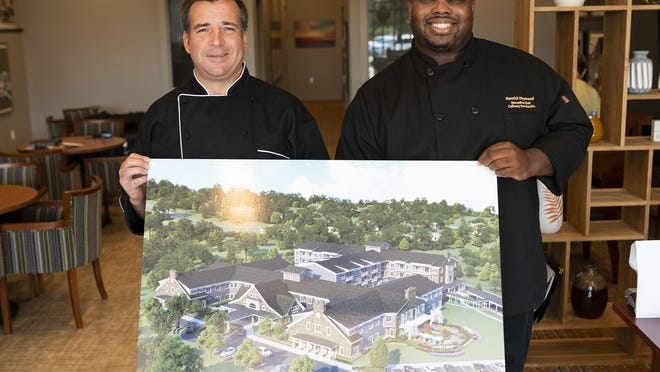 Sous chef Shawn Colena, left, and executive chef Ken Haywood hold an artist's rendering of Artisan at Hudson, which is scheduled to open in November. [T&G Staff/Ashley Green