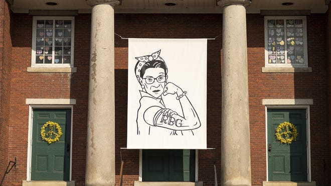 A portrait of the late Supreme Court Justice Ruth Bader Ginsburg, painted in the likeness of Rosie the Riveter, hangs in front of the First Parish Church in Fitchburg on Friday.