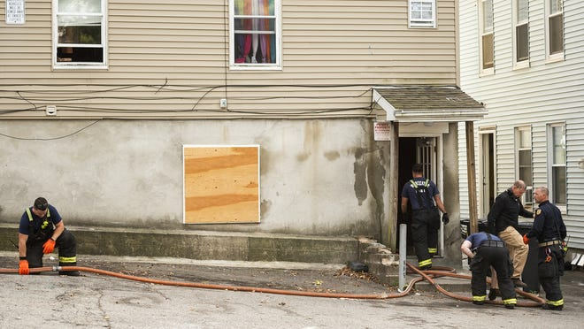 Worcester firefighters pick up hoses after a fire in an apartment building on Vernon Street on Tuesday.
