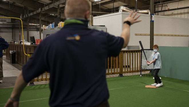 Worcester Bravehearts general manager Dave Peterson throws a pitch to 8-year-old Jordan Fernandes during the new after school program for kids ages 6-12 at Recess Take 2.