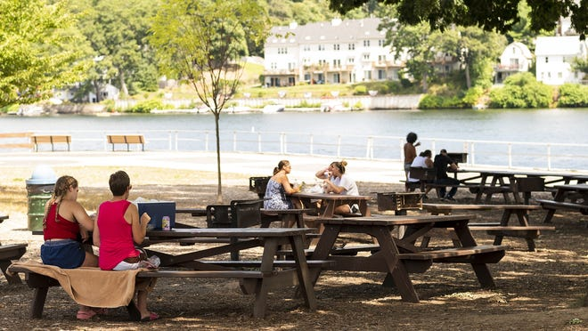 The lunch crowd at Regatta Point at Lake Quinsigamond in Worcester on Wednesday is small, with people spread out at separate picnic tables. Cellphone data confirm that people have fewer personal interactions than they did before the COVID-19 pandemic.
