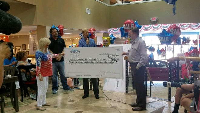 Wilcox Furniture and Sames Ford officials presented Good Samaritan Rescue Mission Executive Director Carole Murphrey (left) and her husband Buddy Murphrey (far right) with proceeds from raffle ticket sales after the drawing Tuesday July 4, 2017.