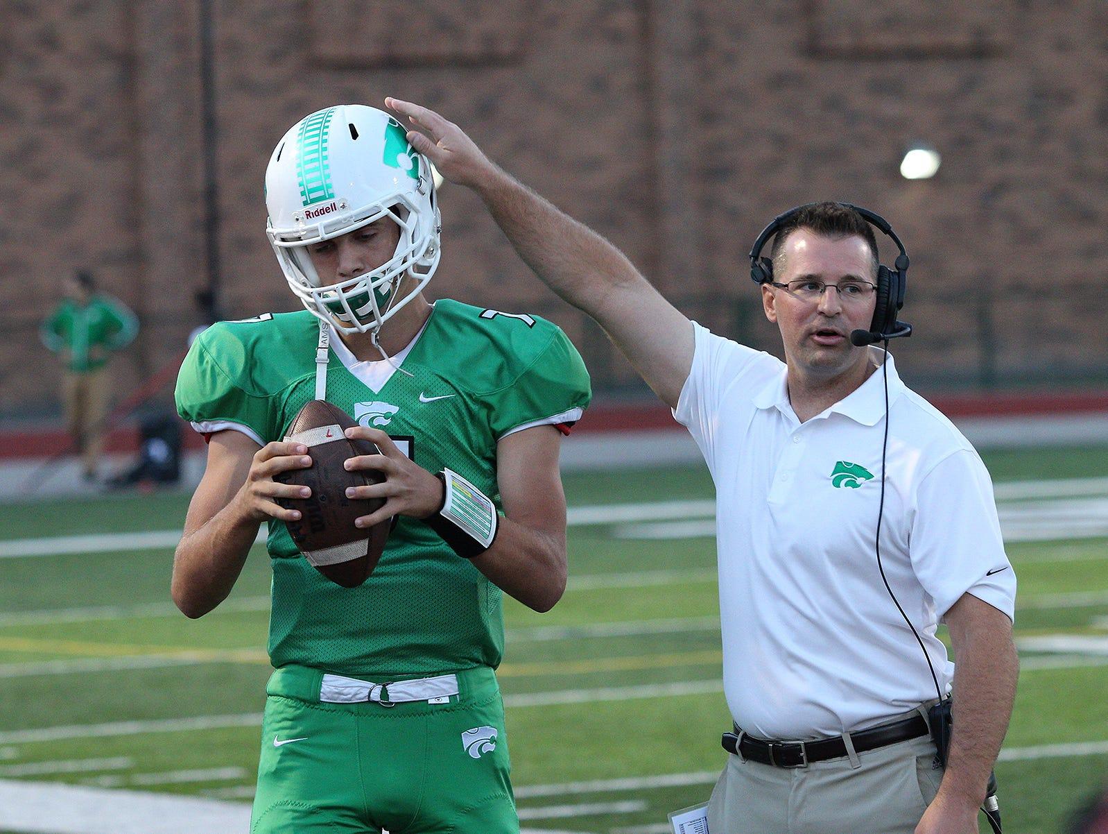 Novi quarterback Alec Bageris warms up alongside an assistant coach before the Novi-Plymouth Salem football game Oct. 7, 2016 at Novi High School.