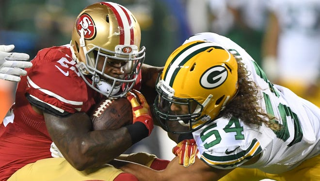 San Francisco 49ers running back Mike Davis is tackled by Green Bay Packers outside linebacker Carl Bradford.