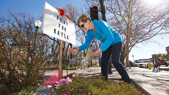 Turi Whiting of Minneapolis leaves a bouquet of flowers