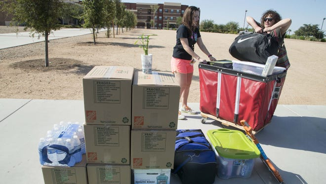 Kaitlin Coffman, a sophomore business major, moves into a dorm at ASU's West campus with the help of her mother, Kathy Coffman , while students attends an orientation in the La Sala Ballroom in the University Centers Building on Tuesday August 18, 2015.