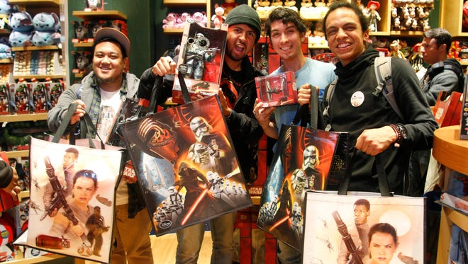 Fans pose with their new Star Wars: The Force Awakens merchandise on Force Friday at a Disney Store in San Francisco, on Friday, Sept. 4, 2015.