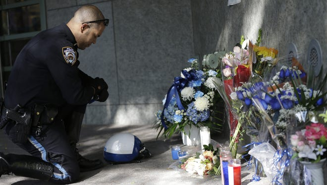 A police officer prays Wednesday at the makeshift memorial to honor Officer Randolph Holder outside a police station in New York.