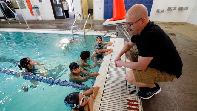 Armando Enriquez, the swim coach at Memorial Park Pool, explains water safety measures to some of his students. April Pools Month will feature instruction, classes and swimming events at area pools to teach about water safety.