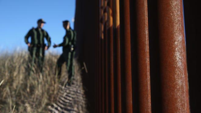 U.S. Border Patrol agents talk next to the United States-Mexico border fence on Dec. 9, 2014, near Nogales, Arizona.