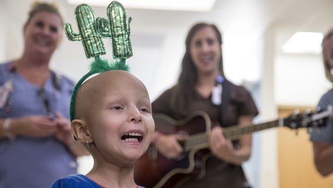 Audrey Hughes, a 4-year-old girl, celebrates her final chemotherapy treatment for cancer after more than a year of weekly treatments at Cardon Children's Medical Center in Mesa. Hughes was diagnosed last year with stage 4 rhabdomyosarcoma, a disease in which malignant cancer cells form in muscle tissue. Audrey continues to defy many odds, as her most recent imaging scan showed no visible sign of cancer after she underwent about 54 weeks of chemo treatment.