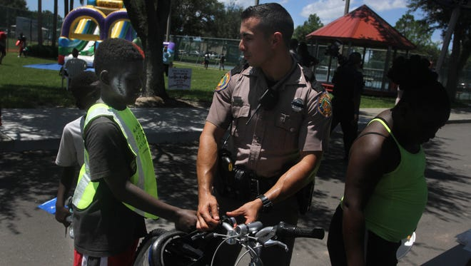 Florida Highway Patrol officer Dan Campisi helps Derrick Cochran, 10, left, put a bell on a bicycle he won in a raffle at the Unity in the Community event at the Stars Complex in Fort Myers on Saturday.