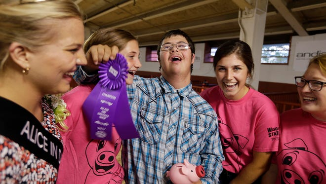 Garret Crowe, a Waukesha West High School student, smiles after he showed a pig at the Wisconsin State Fair. From left, Crystal Siemers-Peterman, the 70th Alice in Diaryland, gives him the ribbon while Isabelle Dougherty and Elysa Dougherty celebrate his success Thursday at the All for One Swine Show.