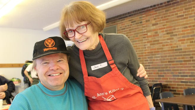 Rosanne Carlile (right) shares a friendly moment with Adrian Larson on the opening day of St. Ann's Kitchen